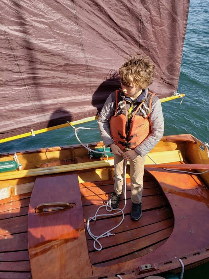 Oscar Barnes at the Helm of his Sailing Dinghy.