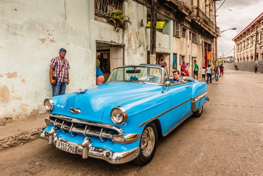 American tourist rides vintage Cuban automobile on tour of Old Havana.