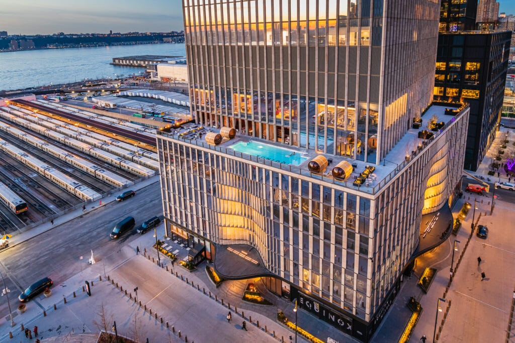 Man watches sunset from Equinox Hotel pool in New York City.