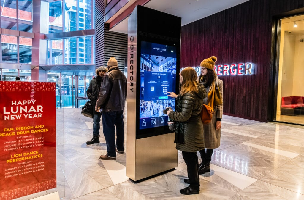 A Hudson Yards Ambassador demonstrates how to order same day tickets at a mall kiosk.