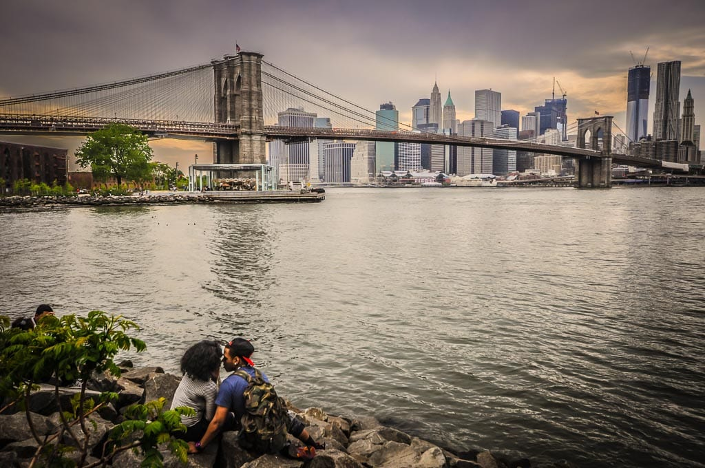 Couple smooches in front of sunset view of the Brooklyn Bridge.