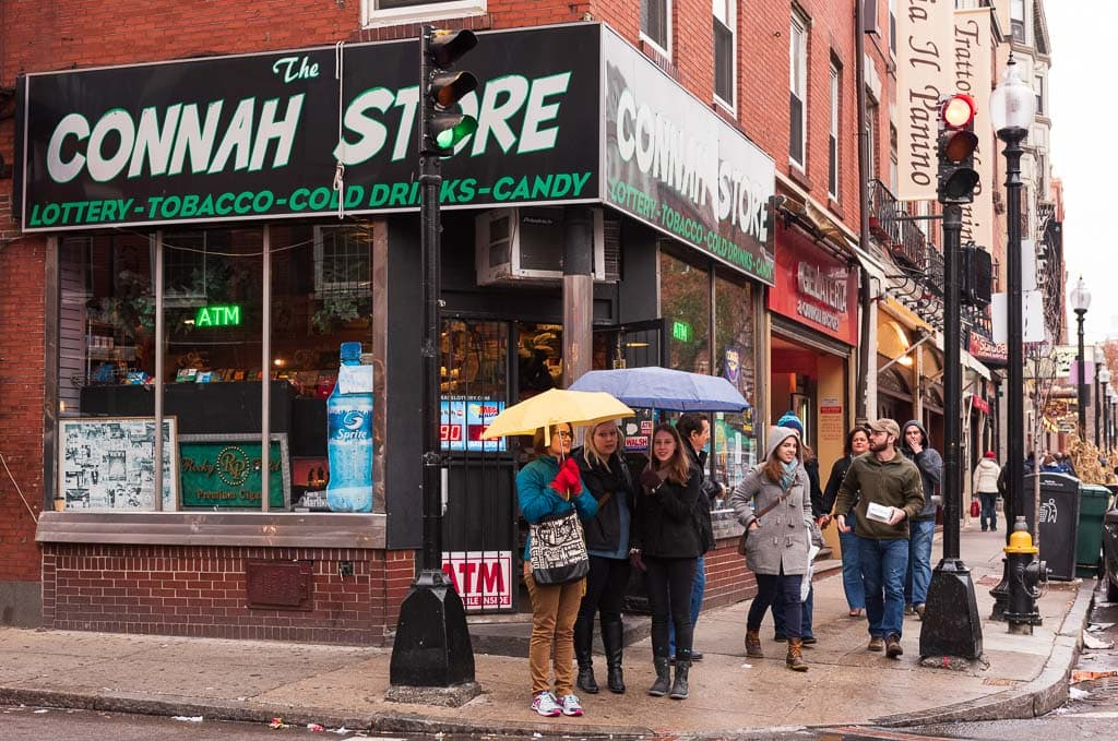 Girls under umbrellas pose in front of The Connah Store in Boston's North End Neighborhood.