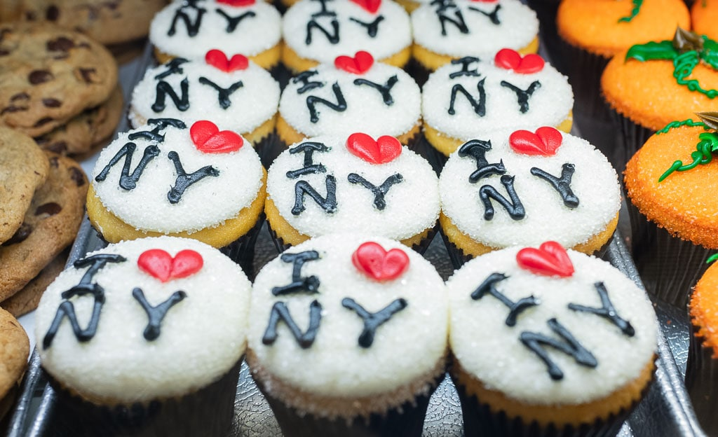 "Tray of cupcakes with white icing that reads ""I Love NY."""