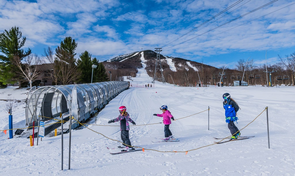 Two kids and instructor at Jay Peak Ski School. They're about to enter the Moving Carpet on a beginner trail.