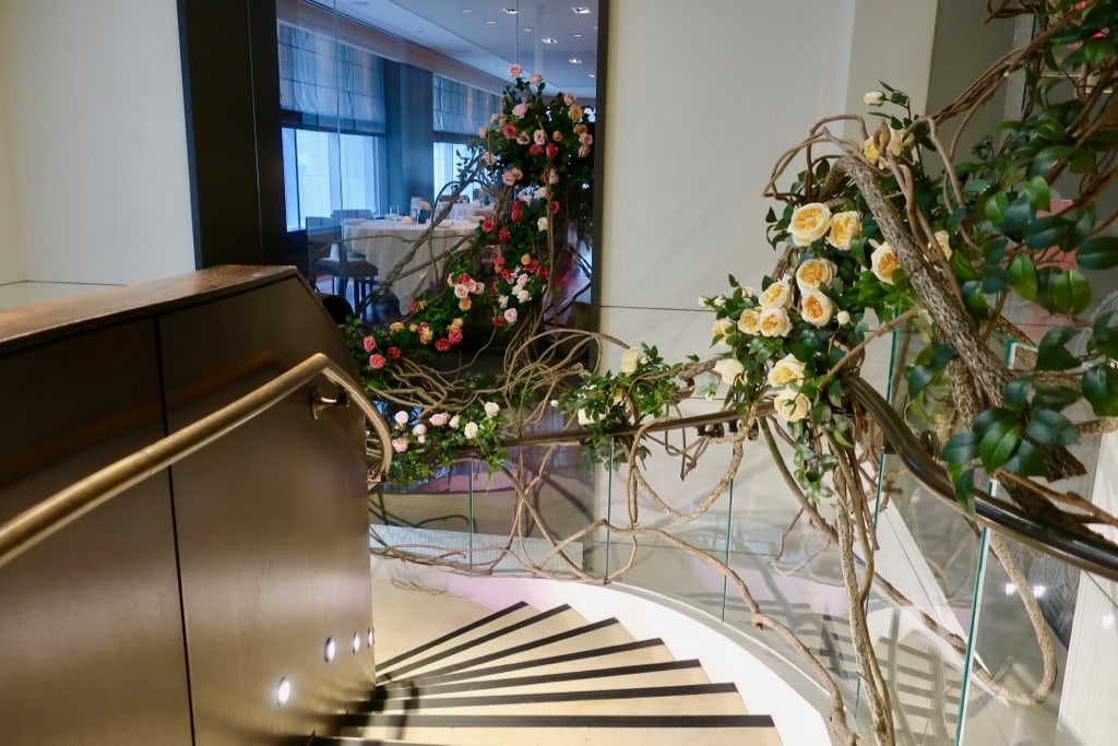 Roses wind on railing of spiral staircase The Langham NY