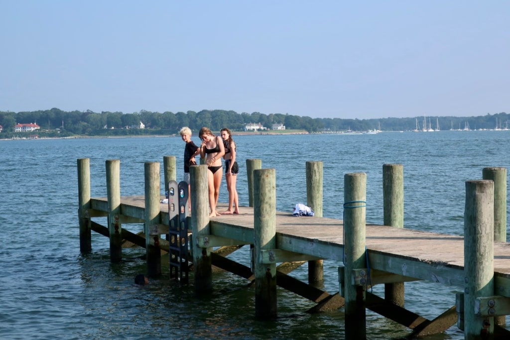 Kids on Peconic Bay pier Summer in the North Fork of Long Island NY