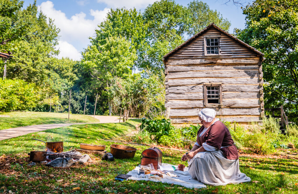 Woman dressed in period clothing demonstrates colonial crafts at Rocky Mount State Historic Site.