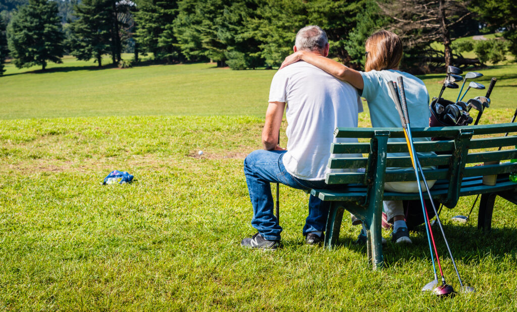 Affectionate couple await turn on golf course at Steele Creek Park