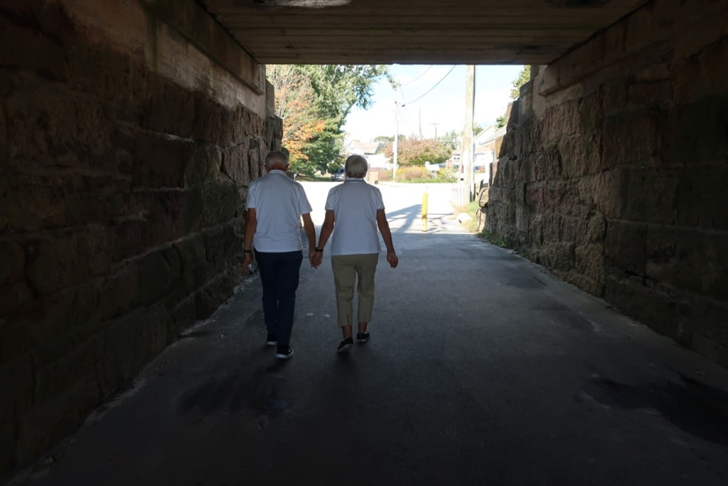Seniors holding hands in Hole in the Wall Beach tunnel Niantic CT